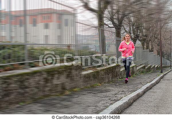 Girl runs on the sidewalk in the city - csp36104268