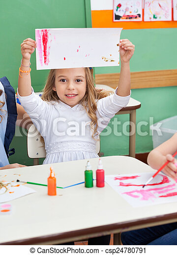 Girl Showing Painting At Classroom Desk - csp24780791