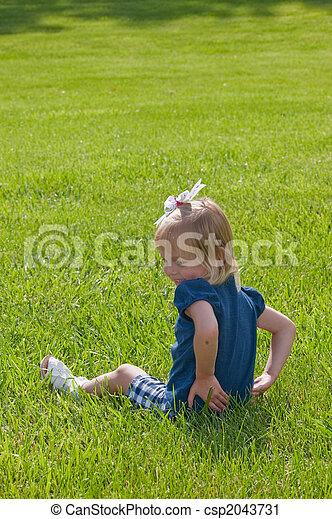 girl sitting in grass - csp2043731