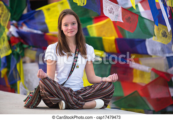 girl sitting in the lotus position on buddhist stupa