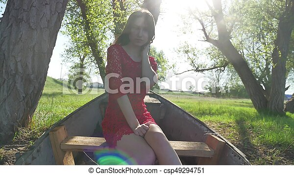 girl sitting in the old boat. lifestyle young woman in a red dress sitting on a old boat on the river in the summer - csp49294751
