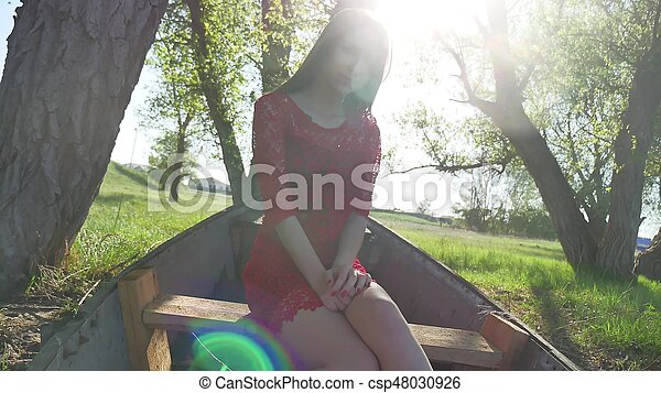girl sitting in the old boat. lifestyle young woman in a red dress sitting on a old boat on the river in the summer - csp48030926