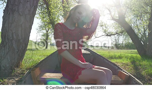 girl sitting in the old boat. young woman in a red dress sitting on a old boat on the river in the summer lifestyle - csp48030864