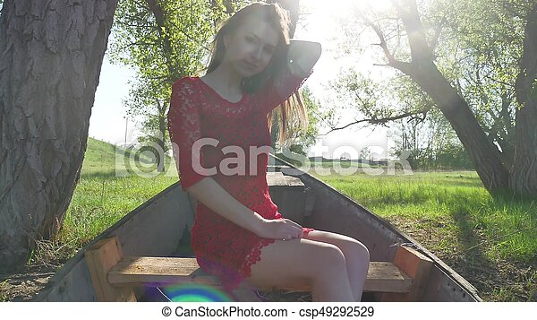 girl sitting in the old boat. young woman in a red dress sitting on a old boat on the river in the summer lifestyle - csp49292529