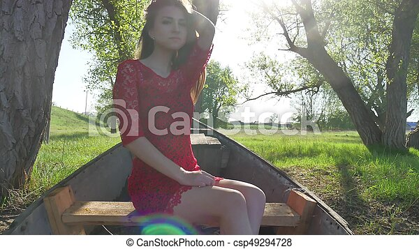 girl sitting in the old boat. young woman in a red dress sitting on a old boat on the river in the summer lifestyle - csp49294728