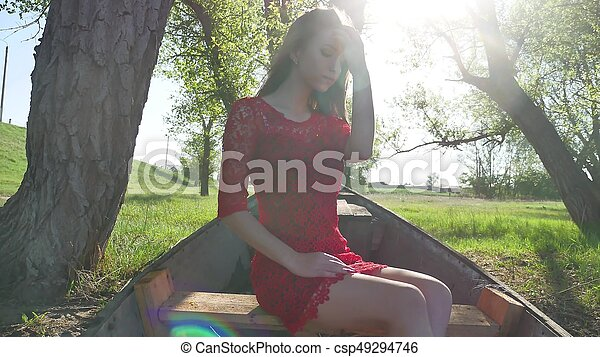 girl sitting in the old boat. young woman in a red dress sitting on a old boat on the river in the summer lifestyle - csp49294746