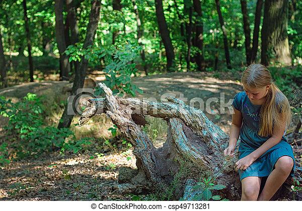 Girl sitting on a tree stump - csp49713281