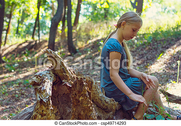 Girl sitting on a tree stump - csp49714293