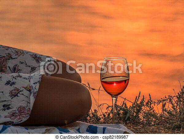 girl sitting with a glass of wine at sunset, a young woman enjoying evening, close up - csp82189987