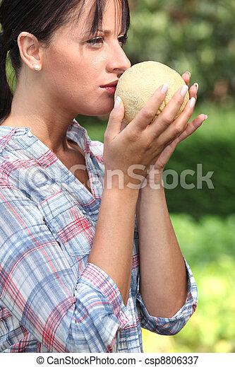 Girl smelling melon - csp8806337
