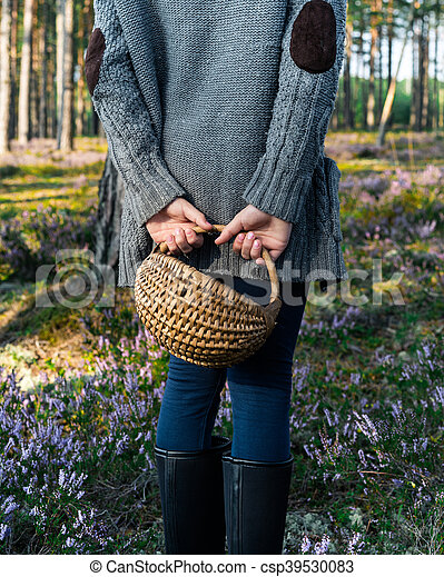 Girl standing back to camera in the forest and holding a basket. - csp39530083