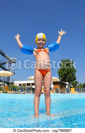 Girl stands in  day-time on skirting in  pool near  hotel and with gladness lifted   hand, underwater package shot - csp7999867
