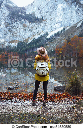 girl stands on the shore of a mountain lake - csp84530580