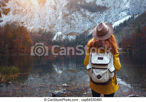 girl stands on the shore of a mountain lake - csp84530460