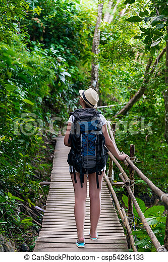 girl tourist with a big backpack in Asia on a wooden trail - csp54264133