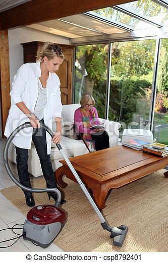 Girl vacuuming for an elderly woman - csp8792401