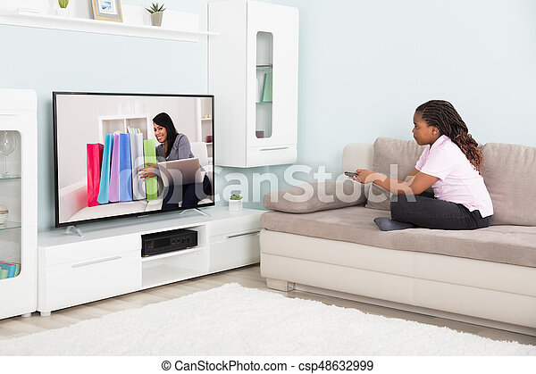 girl watching television  Girl watching television. Girl sitting on couch using remote control ...