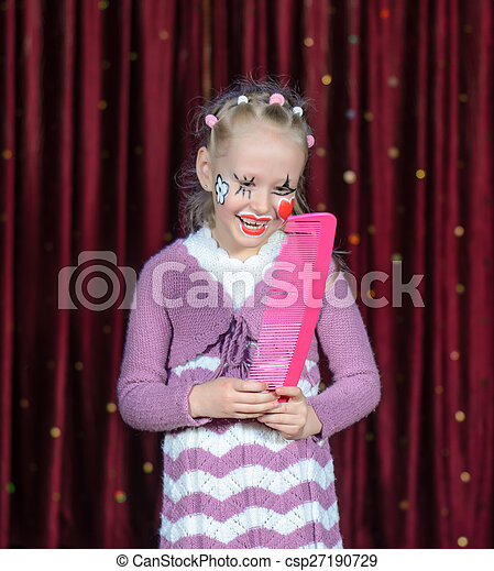 Girl Wearing Clown Make Up Holding Over Sized Comb - csp27190729