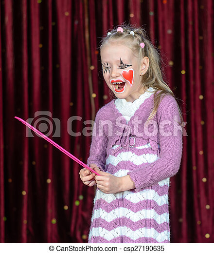 Girl Wearing Clown Make Up Holding Over Sized Comb - csp27190635