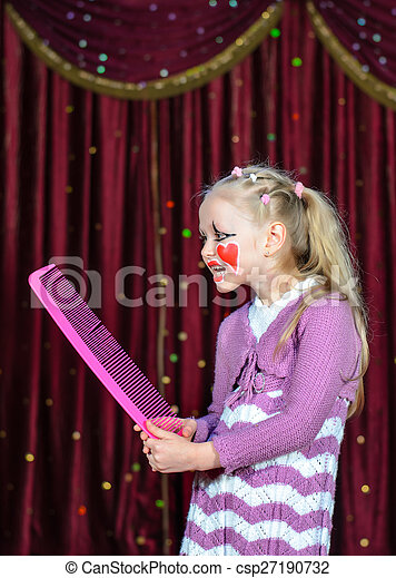 Girl Wearing Clown Make Up Holding Over Sized Comb - csp27190732