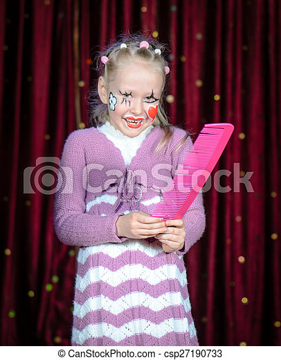 Girl Wearing Clown Make Up Holding Over Sized Comb - csp27190733