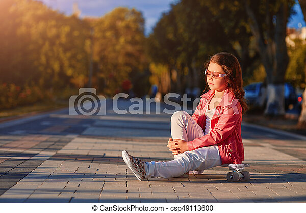 girl wearing helmet sitting on a skateboard in beautiful summer park - csp49113600