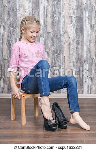 Girl wearing mother shoes. Little