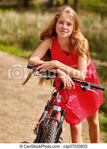 Girl wearing red polka dots dress rides bicycle into park. - csp37033833