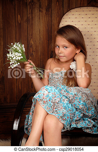 Girl with a bouquet lilies of the valley in chair - csp29018054