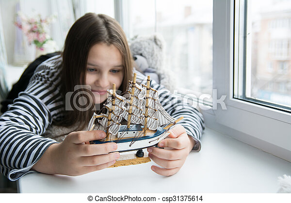 Girl with a ship on the window sill dreaming of voyages - csp31375614