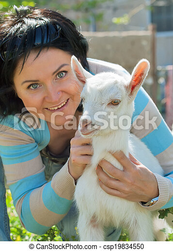 Girl with baby goat. focus at goat - csp19834550