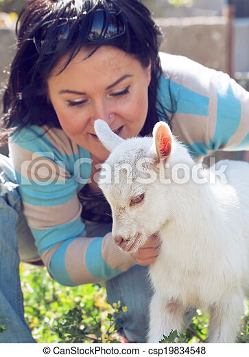Girl with baby goat. focus at goat - csp19834548