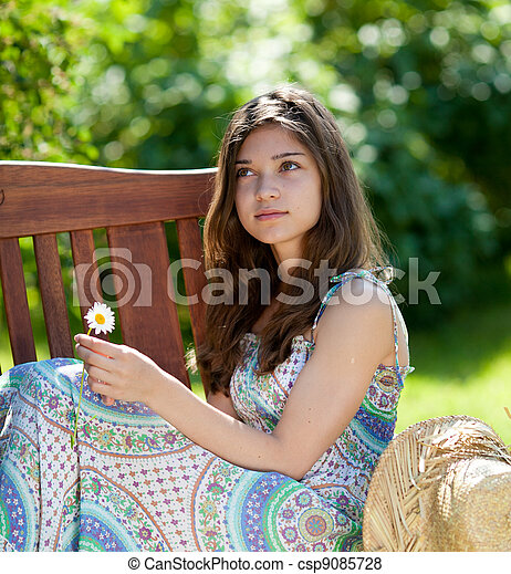 Girl with camomile flower sitting outdoor in summer day - csp9085728