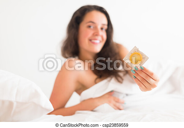 Girl with condom in bed - csp23859559