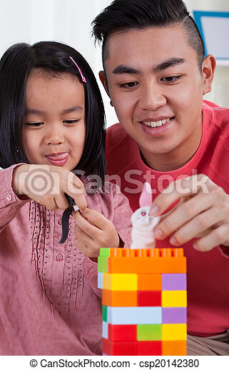 Girl with her brother playing toy blocks - csp20142380
