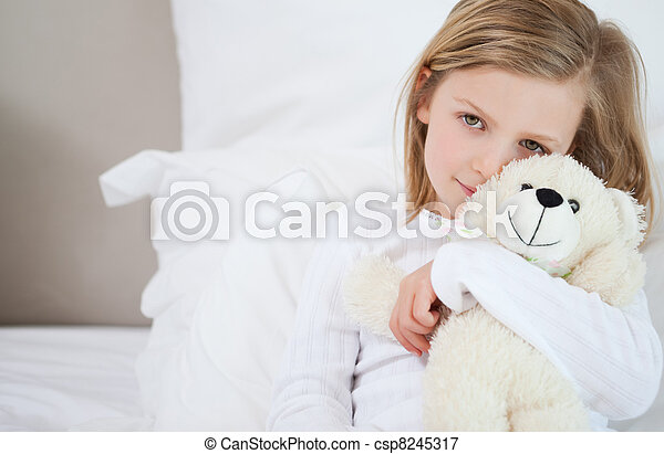 Girl with her teddy sitting on the bed - csp8245317