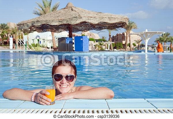 Girl with orange juice at resort hotel - csp3139336