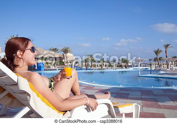 Girl with orange juice at resort hotel - csp3388016