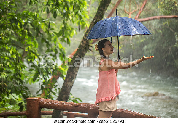girl with umbrella in a rain forest - csp51525793