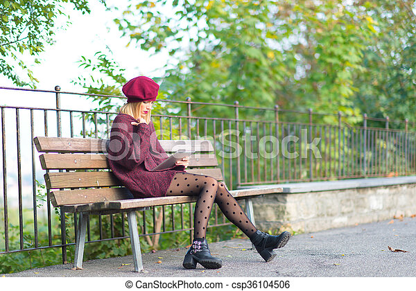 Girl writes on a tablet in the bench - csp36104506