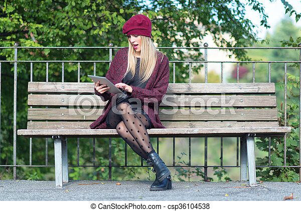 Girl writes on a tablet in the bench - csp36104538