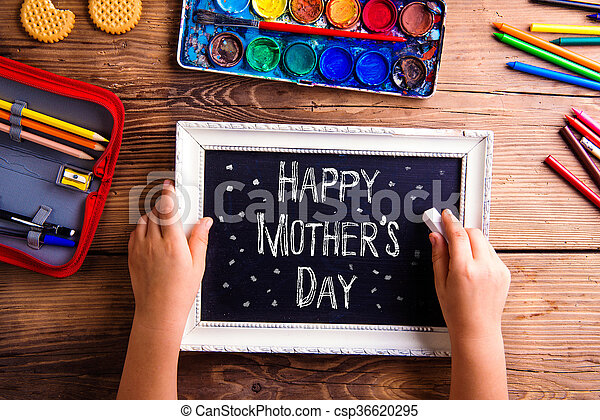 girl writing with chalk on little board mothers day mothers day