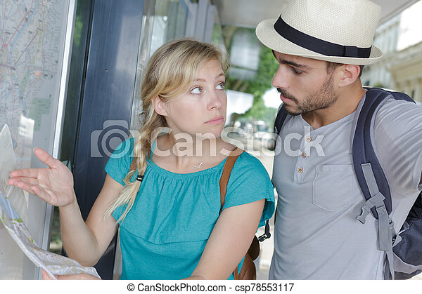 girlfriend showing public transport map to doubtful boyfriend - csp78553117