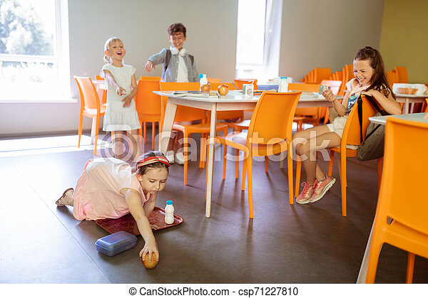 Girls and boy bullying poor little girl dropping apple on floor - csp71227810