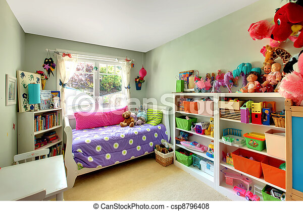 Girls bedroom with many toys and purple bed. - csp8796408