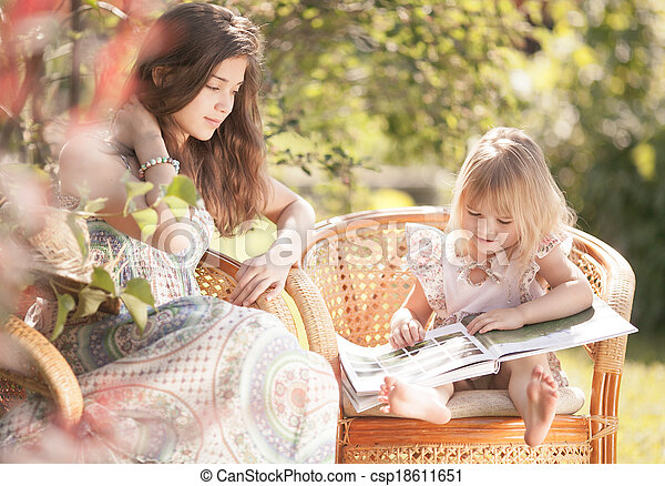 Girls reading book outdoor in summer day. Retro stylized. - csp18611651