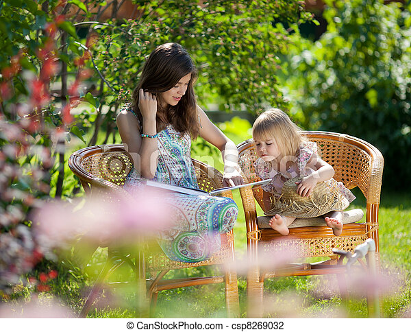 Girls reading book sitting in wicker chairs outdoor in summer day - csp8269032