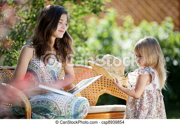 Girls reading book sitting in wicker chairs outdoor in summer day - csp8939854