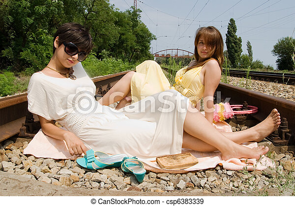 Girls resting on the railroad carelessly - csp6383339