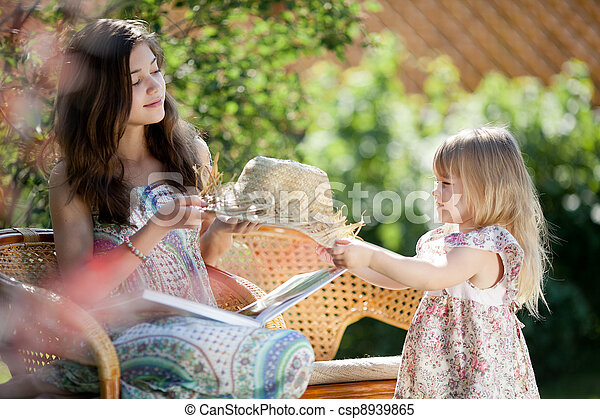Girls with hat sitting in wicker chairs outdoor in summer day - csp8939865